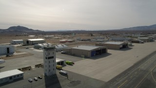 AX0006_070 - Aerial stock footage of 5K aerial  video of passing control tower and hangars at Mojave Air and Space Port in California