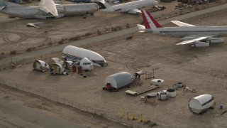 AX0006_074 - 5K stock footage aerial video orbit cabin and cockpit aircraft sections at a desert boneyard, Mojave Air and Space Port, California