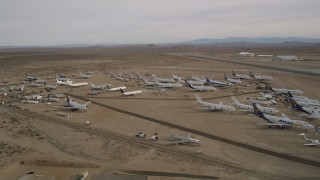 AX0006_077 - 5K stock footage aerial video of large and small airplanes at a boneyard in the desert, Mojave Air and Space Port, California
