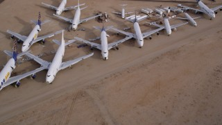 AX0006_079 - 5K stock footage aerial video fly over several jet airplanes at an aircraft boneyard in the Mojave Desert, California