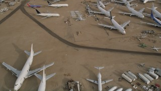 AX0006_079E - 5K stock footage aerial video fly over several jet airplanes at an aircraft boneyard in the Mojave Desert, California