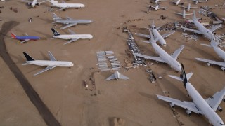 AX0006_080 - 5K stock footage aerial video fly over jets of various sizes at an aircraft boneyard in the Mojave Desert, California