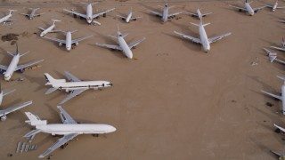 AX0006_081 - 5K stock footage aerial video flying over jets at an aircraft boneyard in the Mojave Desert, California