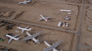 AX0006_082 - 5K stock footage aerial video circle over planes at an aircraft boneyard in the Mojave Desert, California