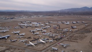 AX0006_083 - 5K stock footage aerial video orbit aircraft at a boneyard by Mojave Air and Space Port in California