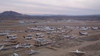 AX0006_084 - 5K stock footage aerial video of an aircraft boneyard and small airport in the Mojave Desert, California