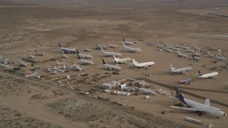 AX0006_086 - 5K stock footage aerial video of airplanes and components at an aircraft boneyard, Mojave Air and Space Port, California