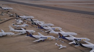 AX0006_087 - 5K stock footage aerial video approach group of jet airplanes at a boneyard in the desert, Mojave Air and Space Port, California