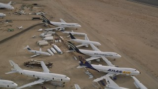 AX0006_087E - 5K stock footage aerial video approach group of jet airplanes at a boneyard in the desert, Mojave Air and Space Port, California