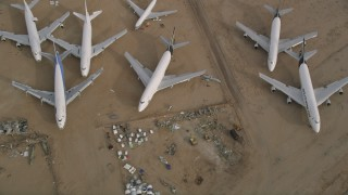 AX0006_090 - 5K stock footage aerial video bird's eye view of a group of airplanes at a boneyard in the desert, Mojave Air and Space Port, California