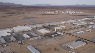 AX0006_094 - 5K stock footage aerial video orbit of runways and a row of hangars at a small airport in California's Mojave Desert
