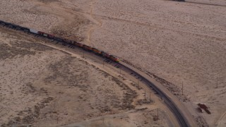 AX0006_095 - 5K stock footage aerial video of cargo train on a curved track in the Mojave Desert, California