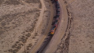 AX0006_096 - 5K stock footage aerial video orbit a cargo train on a curved track in the Mojave Desert, California