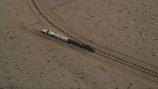 AX0006_097 - 5K stock footage aerial video approach tanker train on a side track in Mojave, California