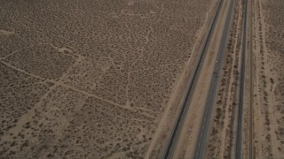 AX0006_099 - 5K stock footage aerial video reverse view of a Highway 14 and open desert in Antelope Valley, California