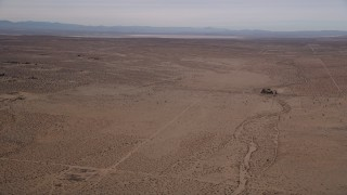 AX0006_121 - 5K stock footage aerial video pan across open desert to reveal a dry lake in Mojave Desert, California