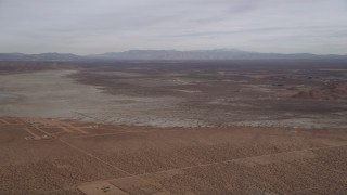 AX0006_130 - 5K stock footage aerial video tilt up to reveal a dry lake in the Mojave Desert, California