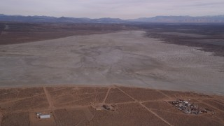 AX0006_131 - 5K stock footage aerial video approach a dry lake in the Mojave Desert, California