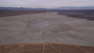 AX0006_132 - 5K stock footage aerial video approaching a large dry lake in the Mojave Desert, California