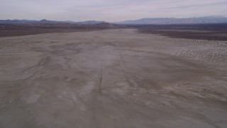 AX0006_133 - 5K stock footage aerial video descend and fly over a desert dry lake in California's Mojave Desert