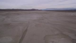AX0006_134 - 5K stock footage aerial video of flying low altitude over a desert dry lake, El Mirage Lake, California