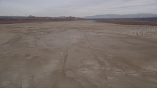 AX0006_134E - 5K stock footage aerial video of flying low altitude over a desert dry lake, El Mirage Lake, California