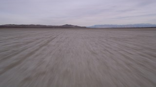 AX0006_135 - 5K stock footage aerial video of racing low altitude over a dry El Mirage Lake in the Mojave Desert, California