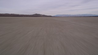 AX0006_137 - 5K stock footage aerial video fly low altitude over a dry lake in the Mojave Desert, El Mirage Lake, California