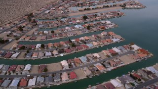 AX0006_167 - 5K stock footage aerial video orbit rows of waterfront homes in the small desert town of Helendale, California