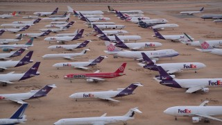 AX0007_007E - 5K stock footage aerial video orbit rows of FedEx cargo planes at a desert boneyard at Victorville Airport, California at Sunset