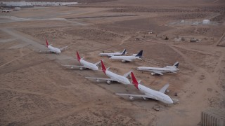 AX0007_013 - 5K stock footage aerial video orbit seven airliners parked at aircraft boneyard in Sunset, Victorville Airport, California