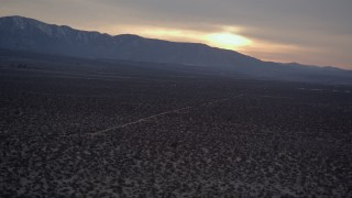 AX0007_032 - 5K stock footage aerial video orbit power lines and desert road at twilight in the Mojave Desert, California