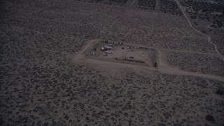 AX0007_040 - 5K stock footage aerial video orbit a small group of RVS in the Mojave Desert at twilight, California
