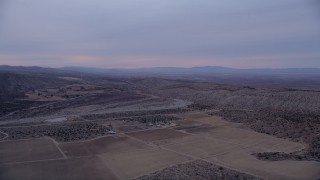 AX0008_002 - 5K stock footage aerial video approach a dry riverbed at twilight in the Mojave Desert, California