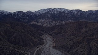 AX0008_003 - 5K stock footage aerial video fly over a dry riverbed toward rock formations and snowy mountains at twilight, San Gabriel Mountains, California
