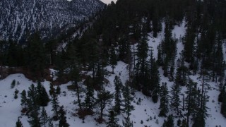 AX0008_030 - 5K stock footage aerial video fly over the San Gabriel Mountains with winter snow and trees at twilight, California