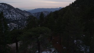 AX0008_032 - 5K stock footage aerial video fly over evergreens and winter snow in the San Gabriel Mountains at twilight, California