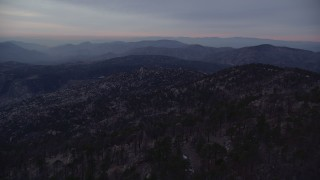 AX0008_034 - 5K stock footage aerial video fly over mountain with trees and snow patches, San Gabriel Mountains at twilight, California
