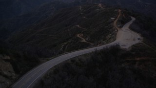 AX0008_045 - 5K stock footage aerial video fly over road and power lines at twilight in the San Gabriel Mountains, California