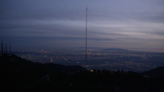 AX0008_057 - 5K stock footage aerial video orbiting radio tower on a mountain in the San Gabriel Mountains at twilight, California