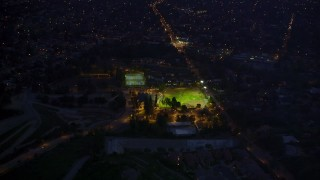 AX0008_065 - 5K stock footage aerial video approach baseball field at night in Altadena, California