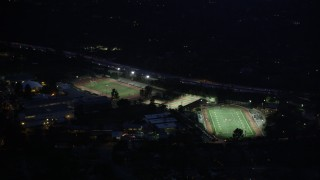 AX0008_067 - 5K stock footage aerial video approach football and track fields at night in La Cañada Flintridge, California