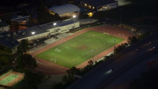AX0008_069 - 5K stock footage aerial video orbit a football field during nighttime practice at La Cañada Flintridge, California