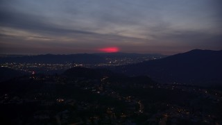 AX0008_071 - 5K stock footage aerial video approach red glow in the clouds above La Cañada Flintridge at night, California