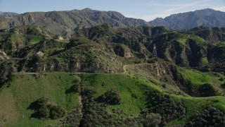 AX0009_002 - 5K stock footage aerial video approach and fly over road and power lines in the San Gabriel Mountains, California