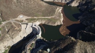 AX0009_016 - 5K stock footage aerial video of approaching Big Tujunga Dam and Reservoir in the San Gabriel Mountains, California