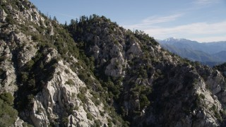 AX0009_034 - 5K stock footage aerial video approach and fly over rocky slopes with trees in the San Gabriel Mountains, California