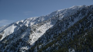 AX0009_058 - 5K stock footage aerial video pan across a snowy peak in the San Gabriel Mountains in wintertime, California