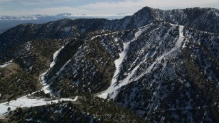 AX0009_066 - 5K stock footage aerial video approach snowy slopes of Mount Baldy Ski Lifts, California