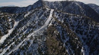 AX0009_067 - 5K stock footage aerial video orbit steep ski runs at Mount Baldy Ski Lifts in California with winter snow